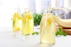 Bottles with tasty melon ball drink. On light table royalty free stock image