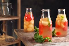 Bottles with tasty melon and watermelon ball drink. On table stock images