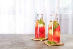 Bottles with tasty watermelon and melon ball drink. On table. Space for text royalty free stock image