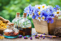 Bottles of tincture and bunch of flowers in wooden box Stock Photo