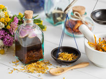 Bottles of tincture and healthy herbs, mortar on table. Stock Photo