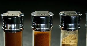 Bottles of various spices 4k. Bottles of various spices on black background 4k stock video footage