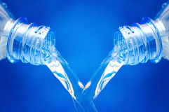 Bottles of water. Bottles with pouring water over blue background royalty free stock photo
