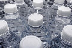 Bottles of Water. Clear plastic bottles of water in several rows with one focused Royalty Free Stock Image