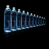 Bottles of water isolated on black background. Several bottles of drinking water isolated on a black background Stock Photos