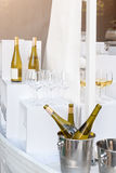 Bottles of white wine standing on serving table. Outdoor party, catering service. royalty free stock photo