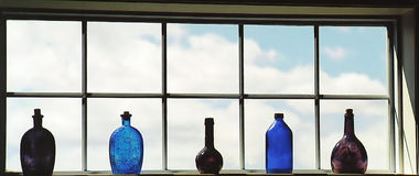 Bottles in the window. Decorative bottles in the window Stock Image