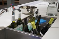 Bottles of wine being cooled in a sink bath full of ice and water stock images