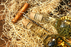 Bottles of wine  with cork screw. Bottles of wine laying on packing straw with cork screw Stock Image