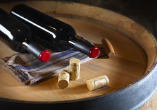 Bottles of wine and corks on a barrel Royalty Free Stock Photos