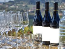 Bottles of wine and glasses with the Langhe countryside. In the background. Langhe is a famous place for good wines and food in Italy stock photo