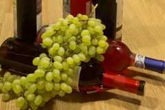 Bottles of wine and grapes. Bottles of wine and grapes on a wooden table stock images