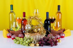 Bottles of wine with grapes and Christmas decorations. On a white top and yellow cloth background Royalty Free Stock Photo