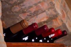 Bottles of wine on wooden shelves in wine cellar. Stock Photo