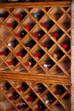 Bottles of wine on wooden shelves in wine cellar. Royalty Free Stock Photography