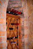 Bottles of wine on wooden shelves in wine cellar. Royalty Free Stock Photos
