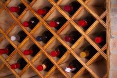 Bottles of wine on wooden shelves in wine cellar. Stock Image