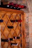 Bottles of wine on wooden shelves in wine cellar. Royalty Free Stock Image