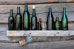Bottles, wineglass and glass stand on a shelf Stock Image