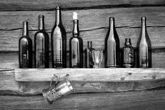 Bottles, wineglass and glass stand on a shelf Royalty Free Stock Image