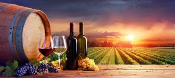Bottles And Wineglasses With Grapes And Barrel. In Rural Scene stock photos