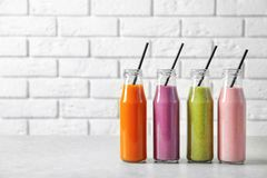 Bottles with yummy smoothie. On table Stock Photos