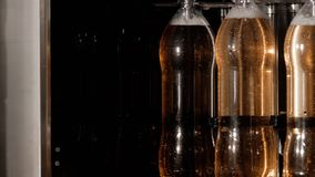 Bottling beverages on automatic conveyor line on factory in plastic bottles.