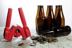 Bottling supplies. Supplies for bottling beer including bottle caps, capper, and empty bottles Stock Photos