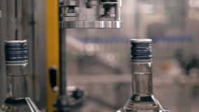 Bottling water on the plant. Cap tightening of vodka on factory bottling plant. Bottling water on the plant stock video footage