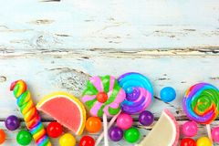 Bottom border of colorful candies against rustic wood Royalty Free Stock Photo