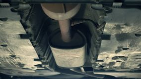 Bottom of the car and exhaust pipe. Maintenance at service station. Bottom of old car and exhaust pipe. Car maintenance at service station Royalty Free Stock Image
