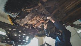 Bottom of car - Worker mechanic checks - automobile service Royalty Free Stock Photos