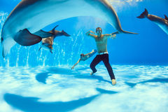 On the bottom of the dolphinarium. Two men and three dolphin fooling around on the bottom of the dolphinarium stock photos