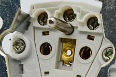 Bottom of electric plug with brass connectors, screws and galvanized frame. 230 Volt european model, artificial lighting royalty free stock images