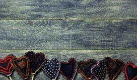 Bottom frame border of Handmade felt hearts on dark old wooden background. Royalty Free Stock Photography