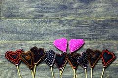 Bottom frame border of Handmade felt hearts on dark old wooden background. Royalty Free Stock Photo