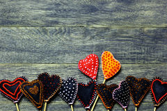 Bottom frame border of Handmade felt hearts on dark old wooden background. stock image