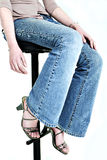 Bottom half. Woman in designer jeans on stool close-up royalty free stock images