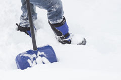 Bottom half of a male in boots and jeans standing in snow with a shovel. Royalty Free Stock Photo