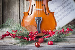 Bottom half of violin with christmas decoration framing it. Royalty Free Stock Images