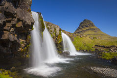 At the bottom of Kirkjufellsfoss waterfall with Kirkjufell mountain in the background Royalty Free Stock Photo