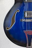Bottom left detail of  guitar. Bottom left detail of blue electric jazz guitar with f-hole and strings Royalty Free Stock Photos