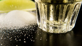 The bottom of a misted glass of tequila. Salt and lime closeup Stock Image