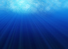 From the bottom of the ocean. Looking up from under water, with sunrays streaming through water surface Royalty Free Stock Photography