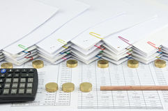 Bottom of pencil with calculator between Pile of gold coins Stock Images