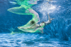 At the bottom of the pool, a woman with a fabric. Royalty Free Stock Photography