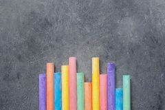 Bottom Rows of Multicolored Chalks on Dark Stone Blackboard Background. Business Creativity Graphic Design Crafts Kids School. Concept. Copy Space stock photography