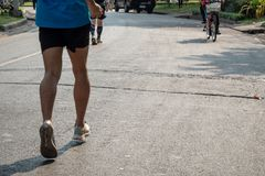 The bottom of the runner who jogging with many people are exercise in the city park  in the morning. The bottom of the runner who wearing blue sport shirt and stock photo