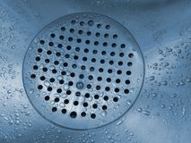 The bottom of a sink filled with water drops stock photography