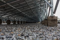 Bottom of the solar panel with the rock in the ground Royalty Free Stock Photography